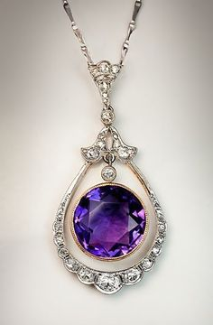 An Edwardian Era Russian Amethyst and Diamond Necklace, Circa 1910. This elegant necklace features a 7.11 carat faceted round Russian amethyst hanging within a drop shaped frame embellished with old European and old rose cut diamonds. In platinum over rose gold, white gold chain. #HathawayTing #HathawayTing's Jewelry