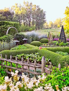 Arches, obelisks, and the varying heights and textures of a rustic cedar fence add interest to the potager, where boxwood trimmed into an X shape establishes the bones of the garden. The potager provides herbs, vegetables, and flowers for cutting