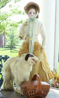 """This is a 13"""" antique French Fashion Doll, circa 1870, and her stylish Borzoi (Russian Wolfhound) companion.  Both are ready for a picnic.  Notice that she also has her binoculars!   We'd like to thank Letha Berry for posting this photo on our Facebook page and giving such a good description.   Letha writes,      """"She is a marked Barrois on rare Terrene kid over wood body with metal arms and bisque hands. Her body type is also known as a baggy pants body. The Barrois firm operated from 1858…"""
