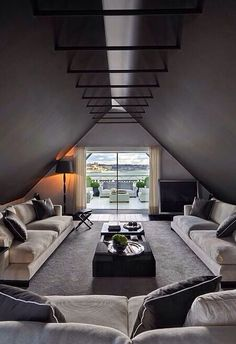 Modern, clean, elegant. Open plan, lots of light, exposed ceiling architecture, neutral monochrome furnishings, large sofas.