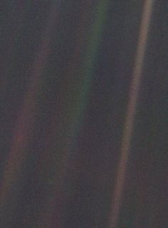 A small pale blue point of light is barely visible on the brown band at the far right, about half way down. Earth as seen in 1990 from 3.7 billion miles away. Photograph taken by Voyager 1.