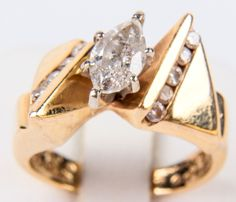"""Lot 10 in the 8.16.16 online & live auction! Stunning 14kt yellow gold diamond wedding / engagement ring with elegant design. Featuring large prong set marquise cut diamond. Band has bow shaped design, accented with 9 round, floating channel set diamonds. Marked """"14k"""", ring size: 7. Total weight: 4.8 dwt. #Jewelry #Fashion #Shopping #POGAuctions"""