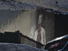 Mural of an older lady and an approaching car reflecting in a puddle of water .