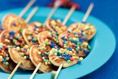 DIY: Bestrijk de poffertjes dun met honing en rijg ze aan een prikker. Bestrooi de spiesjes met de gekleurde bolletjes en het feest kan beginnen!