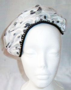 Black and White Polka Dot Hat made by manipulating fabric to create interesting design. Perfect for church, weddings and other special occasions. Trimmed with black and white trimmings.