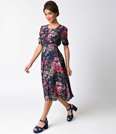 This delightful dress is a pine-worthy 1940s inspired silhouette in a dark navy blue and a bouquet of floral fabrication. A graceful feminine frock, boasting a keyhole neckline, is met above the elbow with ruched sleeves for a charming pop. The entrancing