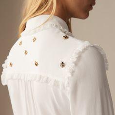 Chemise agrémentée de fines abeilles brodées sur le haut. Col chemise décoré d'un galon en dentelle froncé sur son pourtour. Fermeture à l'aide d'une boutonnière cachée.  Shirt trimmed with fine embroidered bees at the top. Shirt-style collar decorated with a gathered lace braid trim around the edge. Fastened with a concealed button. #maje #ss18 #spring #summer #new #collection #smcp
