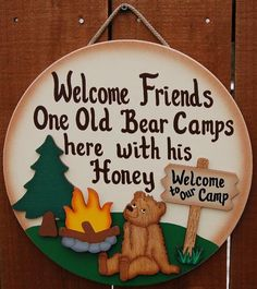 """11 1/2"""" x 11 1/2"""" Camping sign is made from wood and hand painted witha cream colorexterior paint. Letters are painted brown. Bear, fire, tree andthe Welcometo our camp,sign are allseparate piece of wood,whichareattached to the camping sign. It is finished with a light brown shaded edge around the outside, which creates a unique finish. Our camping signs are painted with a very high quality exterior paint, therefor they can be displayed indoors as well as outdoors. You may also…"""