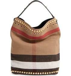 Gleaming studs make this classic Burberry checked bucket bag just right for the season, while a packable cotton-and-jute construction makes it perfect for travel.