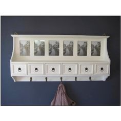 white wall coat hooks and storage drawers photo frames
