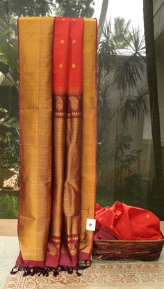 This striking blood red colored gadwal silk has floral bhuttas woven all over in gold zari. The border and pallu are in sangria purple with exclusive gold zari texturing. The sari comes with a cont…