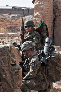 A U.S. soldier kneels behind a wall with an Afghan soldier during a combined foot patrol in Panjwa'i District, Afghanistan, Jan. 29, 2013.