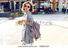 Summer sunny lifestyle fashion portrait of young stylish hipster woman walking on the street, wearing cute trendy outfit, drinking tasty smoothie, smiling enjoy her weekends, travel with backpack/