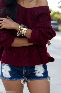 jean shorts, cozy off-shoulder sweater and gold accesories.