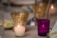 A purple votive holder adds a pop of color to a metallic tablescape.
