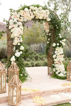 Gorgeous blush El Chorro wedding, in Paradise Valley, Arizona. Light chiffon dress, and coral, pink and white peonies bouquets. Floral archway at the ceremony, and a modern design in petals for the runway. And wooden geometric shapes for decor.