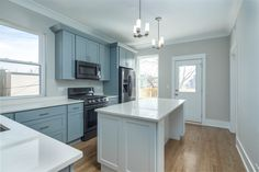 Contemporary farm style kitchen with light blue cabinets, lots of natural light, hardwood floors, black appliances, pendant chandeliers, crown molding, silver hardware, and a large kitchen island with white quartz countertops | Domu Chicago Apartments