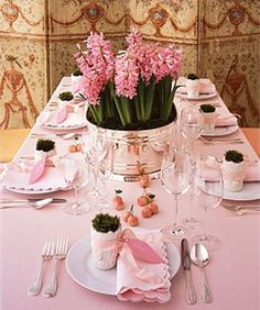 """""""Pretty in Pink"""" table setting is anchored by a virtual garden of hyacinths, planted in a silver-plate tub. Hyacinths, Netherlands Flower Bulb Information Center. Tub, glasses and flatware, all from Broadway Famous Party Rentals, broadwayfamous.com. Tablecloth, $132, Williams-Sonoma, wiliamssonoma.com. Matelassé """"Savannah Gardens"""" napkins, $12 each, Matouk, matouk.com. Moss mounded in white pots, $44/set of four, Oly, olystudio.com. French wire """"Bisque"""" ribbon, Midori, 800-659-3049…"""