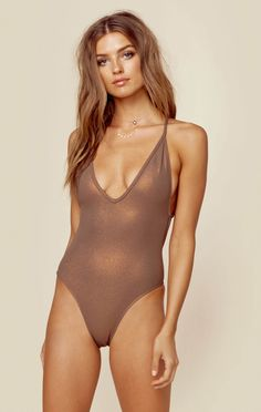 "This sexy new one piece by Blue Life Swim features a plunging neckline with criss cross adjustable straps, subtle glitter contrast throughout, and cheeky exposure.  Made in USAHand WashSpandex Nylon BlendFit Guide:Model is 5ft  8 inches; Bust: 34"", Waist: 25"", Hips: 36""Model is wearing a size XSAdjustable"