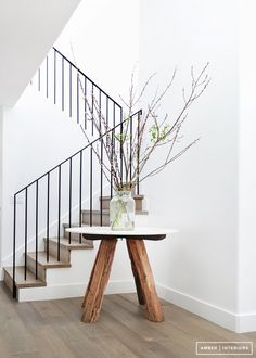 There is always room for natural elements in any decoration. Here we have an ultra clean and modern canvas, with textures from a reclaimed wood table base and willow branches as an arrangement.