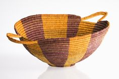 A wide-mouthed woven Indigenous basket. It has a narrow circular base and two double loop handles on opposite sides of the basket lip. The horizontal coil weaving has been coloured in alternating large vertical bands of mustard yellow and purple- brown. Indigenous Art, National Museum, Light Shades, Basket Weaving, Fiber Art, Decorative Bowls, Baskets, Tableware, 14 June