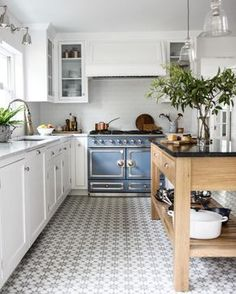 White kitchen, French blue stove, patterned tile floor!
