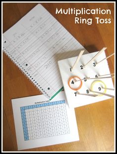 Miniature Multiplication Ring Toss made from bottle-cap rings, styrofoam, number stickers, and popsicle sticks.