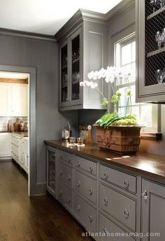 Transitional Modern Grey Kitchen with Butcher Block Counter Tops and wood floors in this galley kitchen