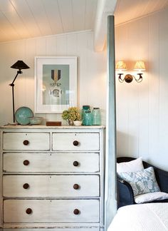 White painted chest of drawers with wooden knobs.