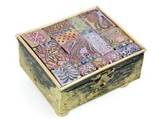 This cigar box has been altered with stamped, air dry or polymer clay, then coloured.