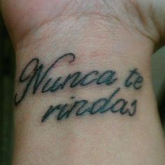 "Little wrist tattoo saying ""Nunca te rindas"", spanish phrase meaning ""Never give up""."