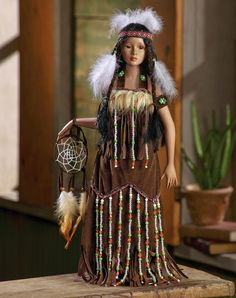 "NATIVE AMERICAN COLLECTOR DOLL, ""HALONA"". SHE WEARS A FAUX BUCKSKIN GOWN AND IS HOLDING A DREAM CATCHER.  AROUND HER HEAD OF LIFE-LIKE HAIR, SHE WEARS A LEATHER AND BEADED HEAD BAND.  HER HEAD, ARMS, HANDS AND FEET ARE FINE BISQUE PORCELAIN.  HALONA COMES WITH A CERTIFICATE OF AUTHENTICITY AND STANDS A FULL 18"" TALL.  THIS IS A COLLECTIBLE, NOT A TOY.  $28.00"