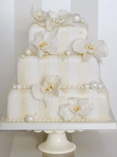 The Liggy's Cake Company - special handmade cakes  Akiko and Pearls A 1920's inspired vintage cake with white and ivory striped icing beautifully finished with delicate sugar orchids and fondant luster pearls. Cake as shown serves 85 guests.