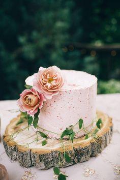 A stunning blush wedding cake with floral cake decor.