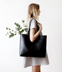 This large modern black tote has natural suede leather interiors.