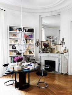 beautifully styled bookshelves + fireplace mantel // low chandelier hung over a little reading table