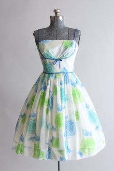 This 1950s/early 1960s Pixie of California cotton sun dress features a blue and lime green floral print. Blue spaghetti straps. Shelf bust.