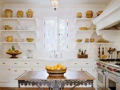 Cottage white kitchen with open shelves & farmhouse sink.  love the island trim!                  In Good Taste:  Nancy Braithwaite Design