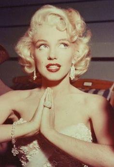 Marilyn Monroe- Ruthie K.   BlackWhite backdrop offset in red chair  White corset top, dia earrings, bracelet (w. charm) large gaudy dia ring    falsies