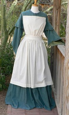 Easy and fun pinner apron often seen in the Colonial through the Civil War Era by ladies. This is a must have if you work around the camps to keep your dress clean and neat.  Made from 100% cotton muslin in natural, white or black.  This pattern is drawn to historical specifications and is the typical apron for the time periods. The skirt is gathered into a half waist and ties in the back. The waist is a tad bit wider than the normal pinner. I did this because I noticed the wider waist looks…