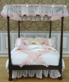 """This """"pretty in pink"""" canopy bed has feminine charm written all over it.  The canopy and dust ruffle are hand pleated white tulle with pink trim. The comforter is made of  white silk taffeta trimmed in pink silk ruffles. A quilted blanket, eyelet sheets, eight matching pillows complete the set!  Bed is vintage solid walnut."""