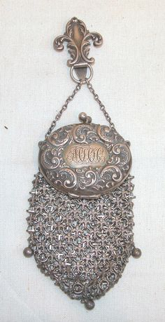 Sterling silver chatelaine purse with fleur-de-lis clip, oval hinged top with scrolling decoration centering a monogram, the bag comprised of silver fleurs-de-lis linked together, ball accents, clip and rim marked, sterling, 6 1/2l.  Condition: no defects observed.