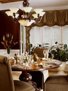 This chocolate-color dining room features brown suede chairs around a round wood table with autumnal table setting and centerpiece. A sconce-like light fixture and large windows with shutter-style blinds illuminate the space.