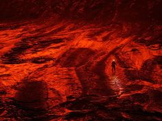 Nyiragongo, Congo. An expedition member walks on cooling lava turned red by the reflective glow of a lake.