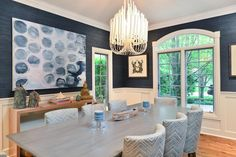 The contemporary chandelier in this dining room adds visual impact to this sophisticated blue dining room.