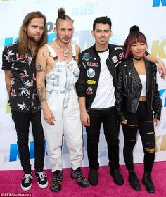 Rising stars: Joe on the other hand arrived with his eclectic band members DNCE earlier on and posed with the eclectic members on the red carpet