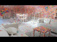 TateShots: Kusama's Obliteration Room: Yayoi Kusama's interactive Obliteration Room begins as an entirely white space, furnished as a monochrome living room, which people are then invited to 'obliterate' with multi-coloured stickers. After a few weeks the room is transformed from a blank canvas into an explosion of colour, with thousands of spots stuck over every available surface.