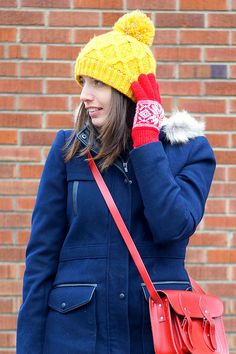 Style On Target | navy winter coat, yellow pom hat, red gloves, red cambridge satchel purse
