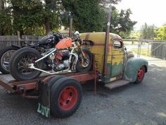 International Harvester IH rat rod pickup truck with dually rear end, stacks, flat bed loaded with two hardtail rat bikes on the back.