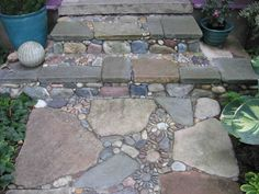 this is it! stepping stones with pebble mosaics made into flower shapes scattered throughout. a bit a whimsy, a bit of the children's creativity it lets the guest know a whole lot about us before they even walk in the door! to the right will be our fairy garden.